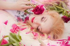 Beautiful romantic young woman in a wreath of flowers posing on a background of roses. Inspiration of spring and summer. Perfume, cosmetics concept stock image