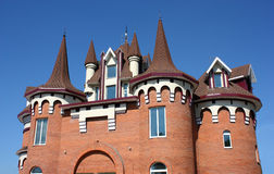 Beautiful roof. The house with a beautiful roof with windows and carved domes from a red brick Royalty Free Stock Images