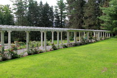 Beautiful rose arbor and landscaped yard, Yaddo Gardens,Saratoga Springs,New York,2015. Beautiful scene of stone and wood rose arbor in the midst of landscaped Royalty Free Stock Image