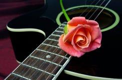 beautiful rose and black acoustic guitar. Symbols of love.