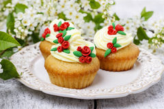 Beautiful rose cupcakes and bird cherries in the background Stock Photos