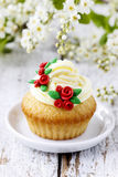Beautiful rose cupcakes and bird cherries in the background Royalty Free Stock Photo