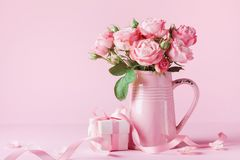 Beautiful rose flowers in pink vase and gift box for Womens day or Mothers day greeting card. Beautiful rose flowers in pink vase and gift box for Womens day or royalty free stock image