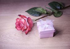 Beautiful rose and gift box on a wooden background Royalty Free Stock Images
