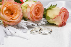 Beautiful rose and wedding rings. On a background white silk Royalty Free Stock Images