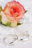 Beautiful rose and wedding rings. On a background white silk Royalty Free Stock Image