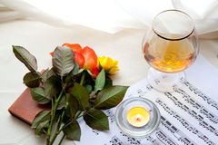 Beautiful roses. Three beautiful roses with music notes, glass and burning candle Royalty Free Stock Image