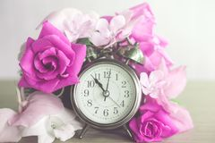 Beautiful roses flowers and clock in purple vintage tone stock photos