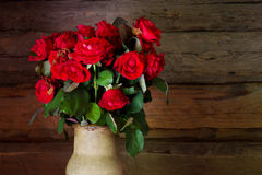 Beautiful roses with frech and wilted buds in ceramic jug on rus Royalty Free Stock Photos