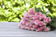 Beautiful roses lying on a wooden table Stock Image
