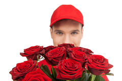 Beautiful roses for you! Close-up of deliveryman holding a bunch Royalty Free Stock Images
