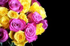 Beautiful round bouquet of pink and uellow roses isolated on black background top view. Beautiful round bouquet of pink and uellow roses flowers on left side of Stock Photography