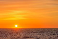 Beautiful round and bright sun setting against a vivid orange sk Royalty Free Stock Image