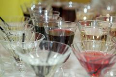 Beautiful row line of different colored alcohol cocktails on a party, martini, vodka,and others on decorated catering bouquet royalty free stock images
