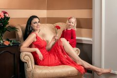 Beautiful royal woman in a luxurious dress with her daughter. royalty free stock images
