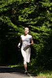 Beautiful running girl. Female runner jogging during outdoor workout on trail in park or forest. Royalty Free Stock Images