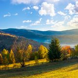 Beautiful rural area in mountains. Gorgeous autumn sunrise with beautiful light, fluffy clouds on the blue sky and some fog in the valley royalty free stock photography