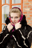 Girl is bundled up against the cold in a fur coat Stock Images