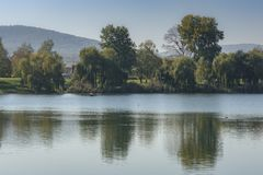 Beautiful rural landscape with a calm water surface. In the distance is a line of forest mountains. In the middle - a strip of green forest, reflected in a stock image