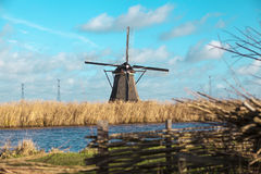 Beautiful rural landscape, fence, field, windmill Dutch windmill. Old windmill stands on the banks of the canal, and water pumps. White clouds on a blue sky Stock Photos