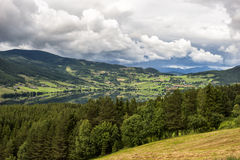 Beautiful rural landscape, field, forest, lake, small houses in the distance, with a beautiful sky, Norway Royalty Free Stock Image
