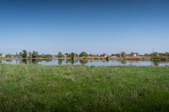 A beautiful rural landscape is a green meadow, a lake and a small village Royalty Free Stock Photos