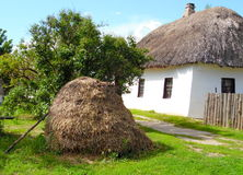Beautiful rural landscape in the Ukrainian village. Ukrainian neat farmhouse with thatched roof and a haystack in front of it Royalty Free Stock Image