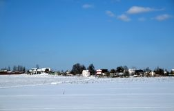 Rural landscape with a village on skyline after snow field under clear blue cloudless sky on bright sunny day. Beautiful rural landscape with a village on Royalty Free Stock Photography