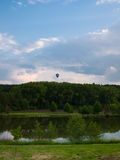 Beautiful rural scenery with floating hot air balloon Royalty Free Stock Image