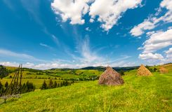 Beautiful rural scenery in mountains. Haystacks on a grassy hillside near the forest on a rolling hills. fine weather with some fluffy clouds on blue summer Stock Photos