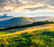 Beautiful rural scenery in mountains at sunrise. Haystack on the field behind the fence. outdated agriculture approach concept stock photography