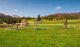 Beautiful rural scenery in springtime. Wooden fence and haystack on a grassy hillside at the foot of Borzhava mountain ridge with snowy tops royalty free stock photography