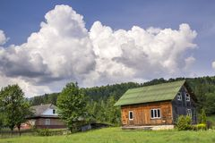 Beautiful Rural Summer Landscape On Bright Sunny Day. Lit By Sun Two Nice Wooden Traditional Ukrainian Houses, Residential And For Royalty Free Stock Images