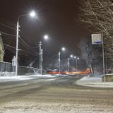 Beautiful rural winter snow-covered street with lanterns on. And light trails from cars. Background royalty free stock images
