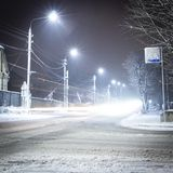 Beautiful rural winter snow-covered street with lanterns on. And light trails from cars. Background stock image