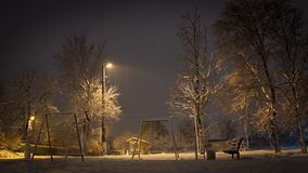 Beautiful rural winter snow-covered street with lanterns on. And light trails from cars. Background stock photography