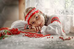 A beautiful Russian girl in a folk costume lay down on the table