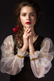 Beautiful Russian girl in national dress with a braid hairstyle and red lips. Beauty face. Picture taken in the studio on a black background Stock Images
