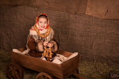 Beautiful russian girl in a shawl  sitting in a cart Royalty Free Stock Image