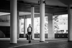 A beautiful Russian girl stands among the tall white columns in the parking lot. Wears black shorts, white jersey and a stock images