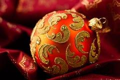 Beautiful rustic christmas ball on red satin Stock Photo