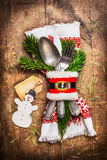 Beautiful rustic Christmas table place setting with cutlery, decorated with napkin, fir twigs , handmade snowman and tag on wooden Royalty Free Stock Image