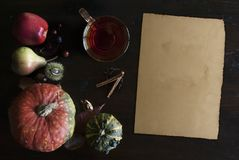 Beautiful rustic fall flat lay with glass of tea, leaves, pumpkins, chestnuts, cup of tea and old paper scroll, on wooden backgrou. Beautiful rustic fall flat Royalty Free Stock Image