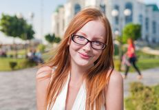 Beautiful 20s aged redhead smiling woman outdoors. Pretty 20s aged redhead smiling joy woman outdoors in glasses royalty free stock image