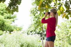 Beautiful 20s girl with binoculars observing her environment Royalty Free Stock Photography