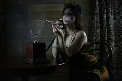 Beautiful 1930s girl smokes. A cigarette at the tabler Royalty Free Stock Photo