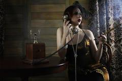 Beautiful 1930s girl smokes. A cigarette at the tabler Stock Photos