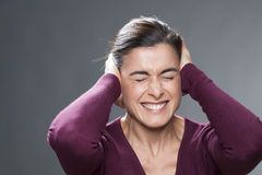 Beautiful 30's girl suffering from migraine covering her ears with her hands Stock Photos