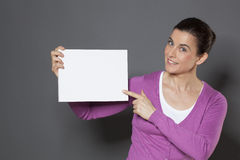 Beautiful 30s woman making an announcement in holding a white insert in front of her Royalty Free Stock Images