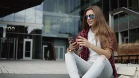 Beautiful 30s woman in stylish glasses sitting on the steps near modern building and listening music stock footage